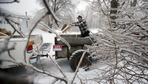 Ken Finnegan loads his truck with firewood as ice clings to trees in Litchfield, Maine. State utility companies had restored power to many who lost it in last week's ice storm by Sunday, but more snow threatened other outages Sunday night into Monday.