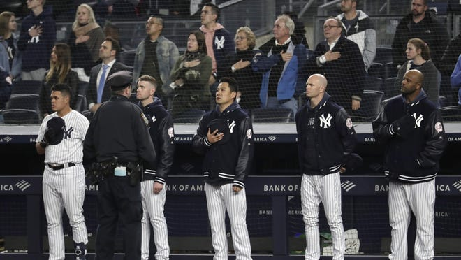 "New York Yankees players listen to ""God Bless America"" during the seventh-inning stretch of the team's baseball game against the Kansas City Royals, Thursday, April 18, 2019, in New York. The Yankees have suspended the use of Kate Smith's recording of the song while they investigate an allegation of racism against the singer."