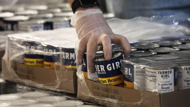 A volunteer uses gloves while moving cans of beans into boxes as he helps pack meals in March for those affected by the COVID-19 pandemic at the Mid-Ohio Foodbank in Grove City.
