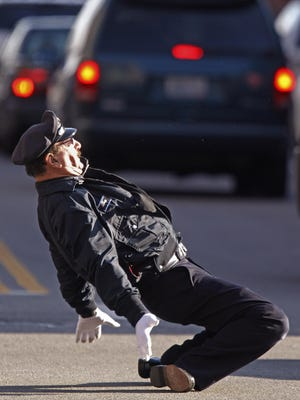 In this Dec. 13, 2012 photo, former Providence Police Department Officer Tony Lepore directs traffic at an intersection in Providence, R.I. Lepore says he was told by police officials Tuesday not to return to city streets to direct traffic during the Christmas season after organizing a protest over the appearance of a Black Lives Matter hashtag on a police officer's coffee cup.