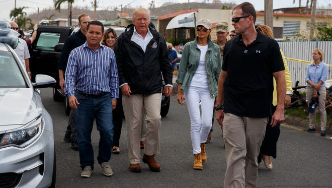 President Donald Trump and first lady Melania tour a neighborhood hit by Hurricane Maria on Oct. 3, 2017, in Guaynabo, Puerto Rico.