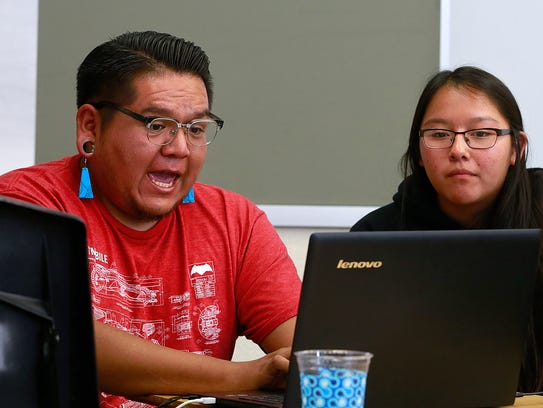 Krieg Benally, left, of Cultivating Coders, helps out