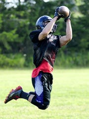Chase Tucker makes a catch during drills at a Sandusky football practice.