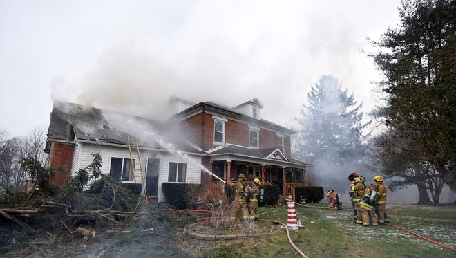 Firefighters work to extinguish a house fire at 16 Vanderbilt Road between Mansfield and Bellville on Friday afternoon. Jason J. Molyet/News Journal