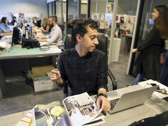 Vogue Arabia staffer Mohammad Hazem Rezq works at his desk at the magazine office in the Dubai Design District in Dubai, United Arab Emirates, Wednesday. Vogue Arabia's debut featured on its cover American supermodel Gigi Hadid, whose father is Palestinian.