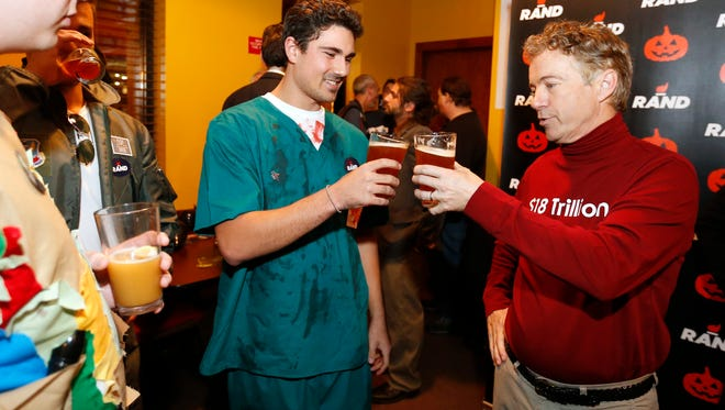 Gene Nassif, dressed as an Obamacare Surgeon (center), clinks drinks with Republican presidential candidate Rand Paul in his $18 Trillion debt shirt after Nassif bought Paul a Confluence Des Moines IPA Friday, Oct. 30, 2015, during the Rand Paul Liberty Halloween Party at Buzzard Billy's in Des Moines.