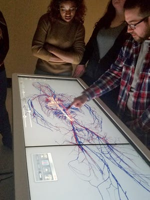 Henry Ford College students Taylor Wiley (left) and Briana Robinson (center) watch classmate Caleb Gatton perform an autopsy on a virtual cadaver on HFC's newly-acquired Anatomage Table.