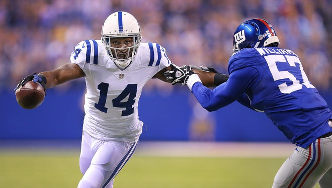 Indianapolis Colts Hakeem Nicks (#14)  stiff-arms NY Giants Jacquian Williams,right,  in the first half of their preseason Saturday, August 16, 2014, evening at Lucas Oil Stadium.