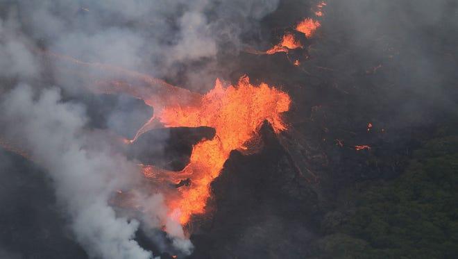 Lava erupts and flows from a Kilauea volcano fissure, towards the Pacific Ocean, on Hawaii's Big Island on May 21, 2018 near Pahoa, Hawaii.
