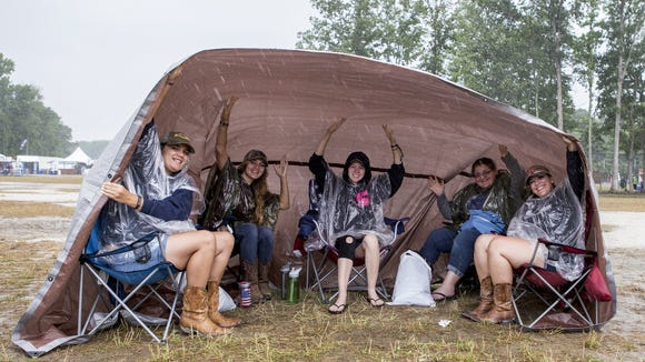 Big Barrel attendees from Lancaster, Pa., gather under a tarp to escape the rain Saturday near the main stage at the Big Barrel Country Music Festival.
