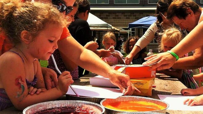 Kids blow bubbles into a pan of colored liquid, then place a sheet of paper over the pan. The popping bubbles create art. This activity run by Lori Lindner was one of many at last year's Summer Lunch & Fun program in North Liberty.