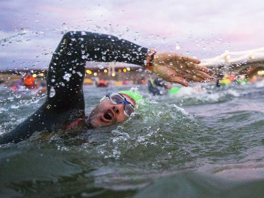 Competitors swim during Ironman Arizona in Tempe, Ariz.