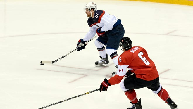 USA forward Phil Kessel (81) skates past Canada defenseman Shea Weber (6) in the men's ice hockey semifinals.