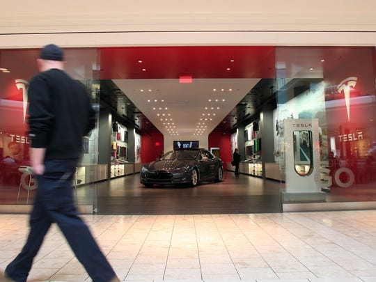 A man walks past the Tesla showroom in the Mall at Short Hills in March.