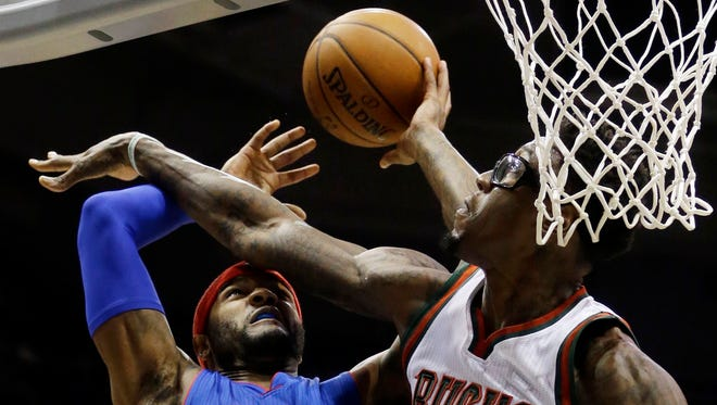 Milwaukee Bucks' Larry Sanders, right, fouls Detroit Pistons' Josh Smith during the first half of an NBA basketball game Tuesday, Nov. 25, 2014, in Milwaukee.