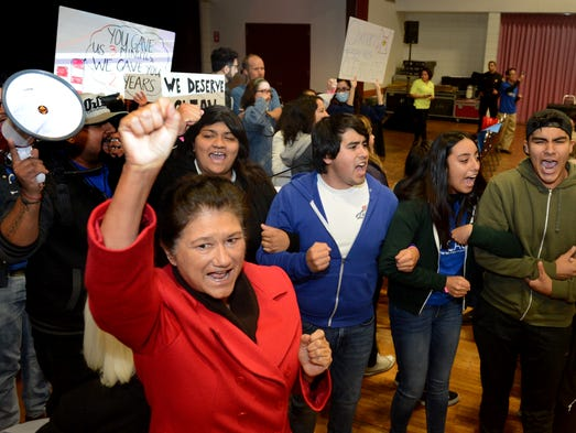 Julie Peña, front, raises her fist in solidarity with
