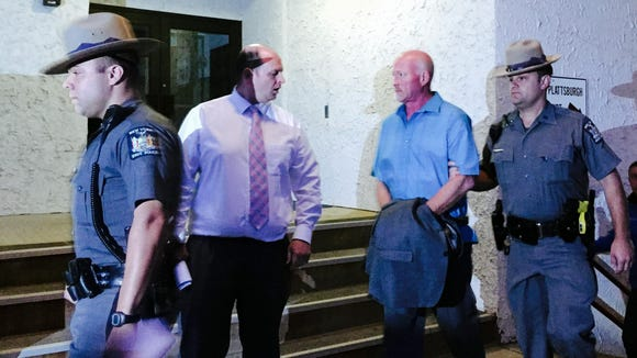 New York State Police officers escort suspended Clinton Correctional Facility guard Gene Palmer from court in Plattsburgh Wednesday, June 24, 2015. Palmer is believed to have delivered tools inside frozen meat to two Clinton inmates before they escaped on June 6. He faces charges including promoting prison contraband and tampering with physical evidence, state police said.