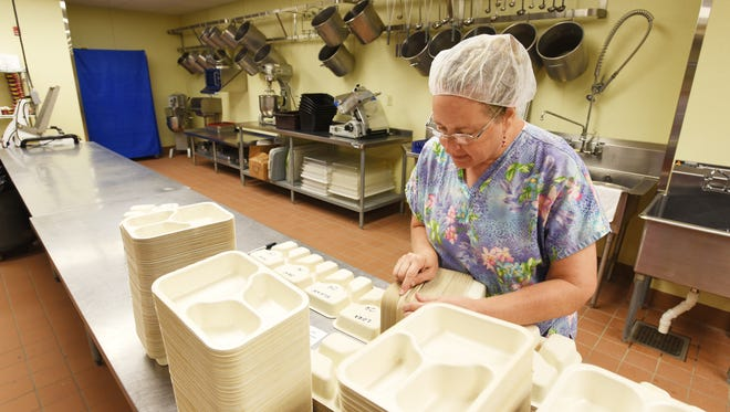Susan Barborak readies trays for home delivery meals at the Muskingum County Center for Seniors on Tuesday.