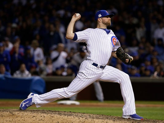 FILE - In this Wednesday, Oct. 18, 2017, file photo, Chicago Cubs relief pitcher Wade Davis throws during the ninth inning of Game 4 of baseball's National League Championship Series against the Los Angeles Dodgers, in Chicago. The Colorado Rockies added a significant piece to what's becoming a formidable and high-priced bullpen by agreeing to a three-year, $52 million contract with All-Star reliever Wade Davis, a person familiar with the negotiations told The Associated Press, on Friday, Dec. 29. (AP Photo/Nam Y. Huh, File)