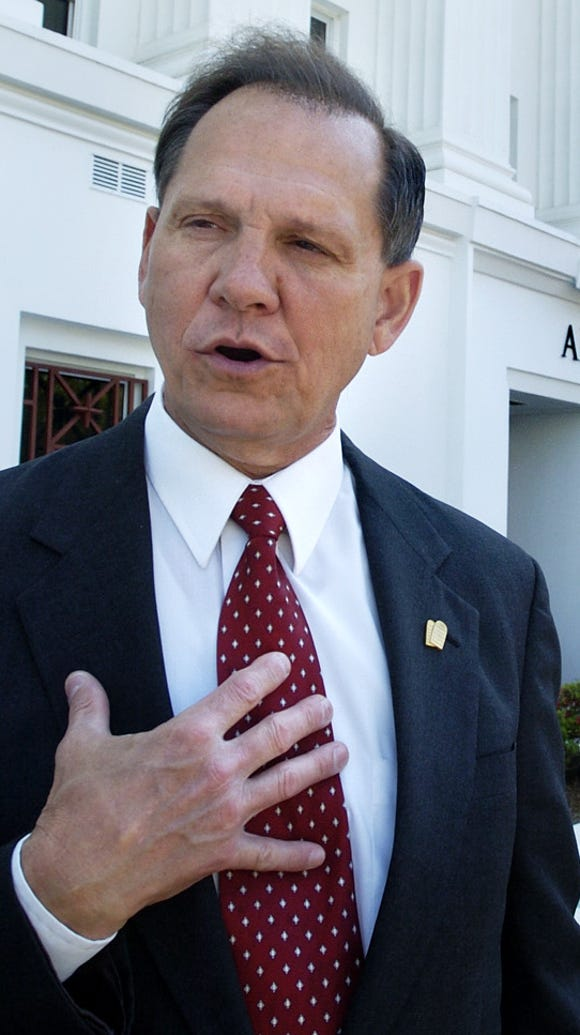 Former Alabama Chief Justice Roy Moore pauses outside