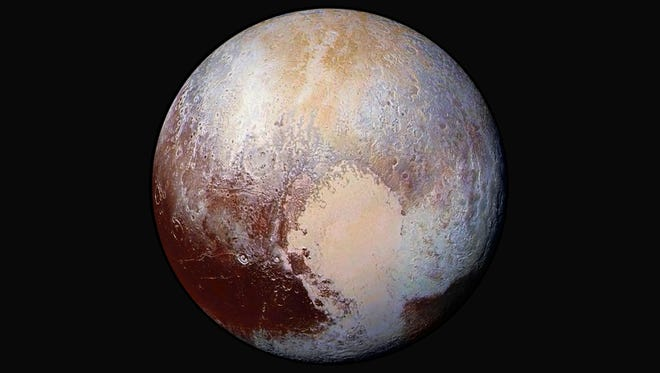 This image made available by NASA on Friday, July 24, 2015 shows a combination of images captured by the New Horizons spacecraft with enhanced colors to show differences in the composition and texture of Pluto's surface.
