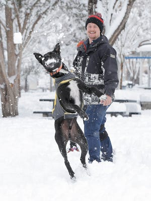 Miles Overstreet throws snowballs to his dog Ferris as they play Sunday morning at Madeline Park in Kern Place. A heavy, overnight snowfall created a winter playground for El Pasoans.