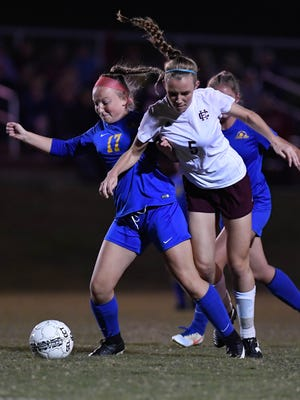 Caldwell's Hannah Young (17) and Henderson's Maddie Griggs (5) try to beat each other to the ball as Henderson County beat Caldwell County 5-0 in the Girls 2nd Region final played at Madisonville North Hopkins High School in Hanson Thursday, October 19, 2017.
