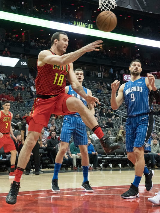 Atlanta Hawks center Miles Plumlee (18) sends a pass past Orlando Magic center Nikola Vucevic (9) as he saves a ball from going out of bounds during the first half of an NBA basketball game, Saturday, Dec. 9, 2017, in Atlanta. (AP Photo/John Amis)