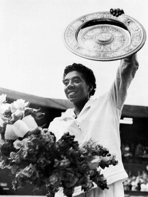 FILE - In this July 5, 1958, file photo, New York's Althea Gibson waves the winner's plate aloft after she defeated Britain's Angela Mortimer in the women's singles tennis final at Wimbledon, England. Gibson won an amazing 11 Grand Slam titles in three years from 1956-58, including the French Open, Wimbledon and U.S. Open.
