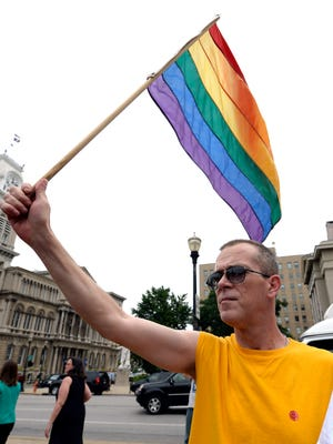 Aaron Bingham of Louisville, Kentucky, waves a rainbow flag during a rally in support of the U.S. Supreme Court decision on the Defense of Marriage Act, June 26, 2013, at Jefferson Square in Louisville, Ky. The justices issued two 5-4 rulings in their final session of the term. One decision wiped away part of a federal anti-gay marriage law that has kept legally married same-sex couples from receiving tax, health and pension benefits. The other was a technical legal ruling that said nothing at all about same-sex marriage, but left in place a trial court's declaration that California's Proposition 8 is unconstitutional.