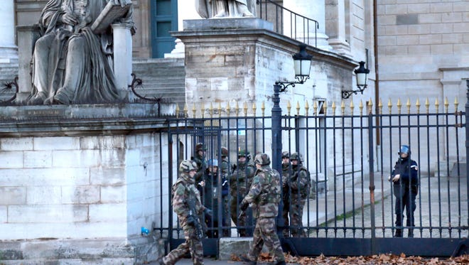French soldiers deployed as part of emergency security measures guard the National Assembly building in Paris, France, Saturday, Nov. 14, 2015. French police are hunting possible accomplices of eight assailants who terrorized Paris concert-goers, cafe diners and soccer fans in this country's deadliest peacetime attacks, a succession of explosions and shootings that cast a dark shadow over this luminous tourist destination.(AP Photo/Jacques Brinon)