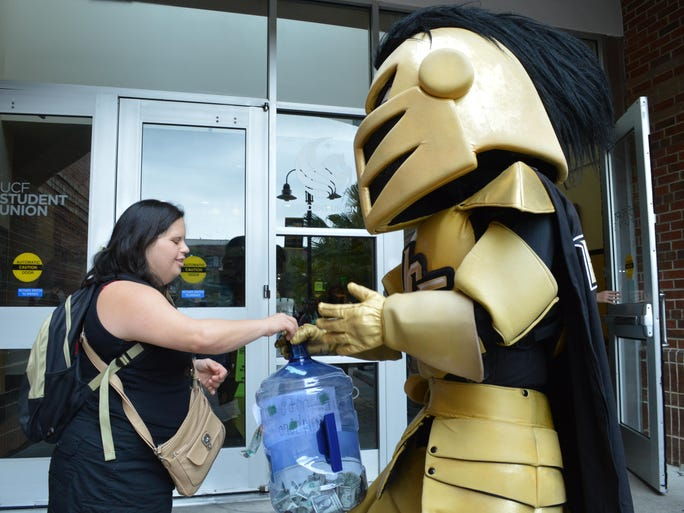 A student donates to Knightro as part of G1VE TODAY