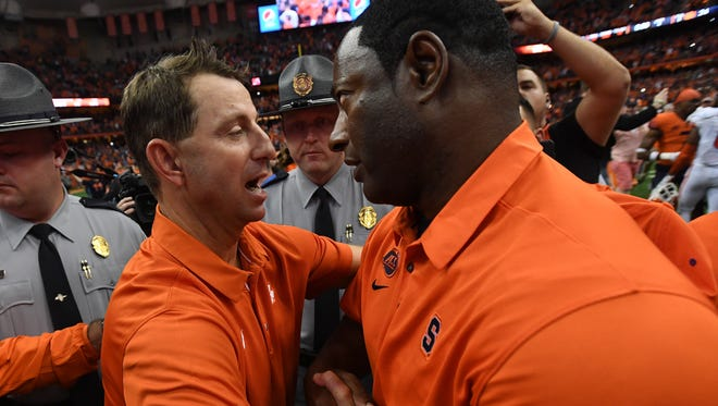 Clemson head coach Dabo Swinney meets Syracuse head coach Dino Babers after the Tigers 27-24 loss on Friday, Oct. 13, 2017 at the Carrier Dome in Syracuse, N.Y.