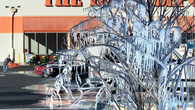 A customer pushes his cart over an icy parking lot at the Home Depot on Capitol Circle West in  Tallahassee in this 2006 photo.  The sprinkler system in their landscaping not only caused their trees and plants to freeze over but drained all over their drive and parking lot causing slippery parking and walking.