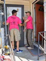 Volunteers help put up a door at a home on Friday as