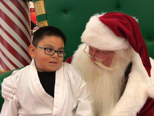 Pedro Solis, 6, reveals to Santa what he really wants for Christmas this year at Holiday Happenings at La Palmera mall.