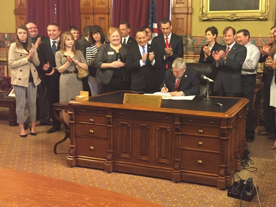 Gov. Terry Branstad signs House File 516, enacting new voter identification requirements for elections.