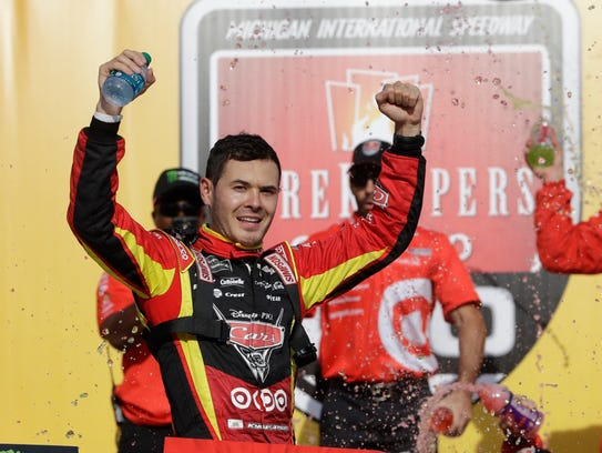 Kyle Larson raises his arms after winning the NASCAR