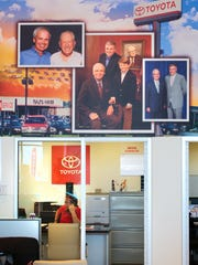 Bruce Goss, a business development center employee for Ralph Hayes Toyota, works underneath a showroom wall with Hayes family photos. The middle photo, left to right, Randolph Hayes, Robert Hayes, Harrison Hayes, and a framed photo of Ralph Hayes. The left photo is of Randolph Hayes and the late Jim Moran, who owned the largest distribution in the Southeast.