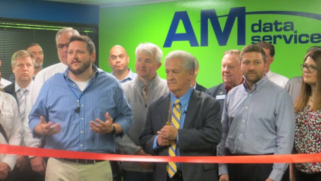 Ian McCain of South Lyon (blue shirt), Livonia Mayor Dennis Wright (wearing tie) and AM Data Services owner Rich Miller help cut the ribbon on the firm's new digs.