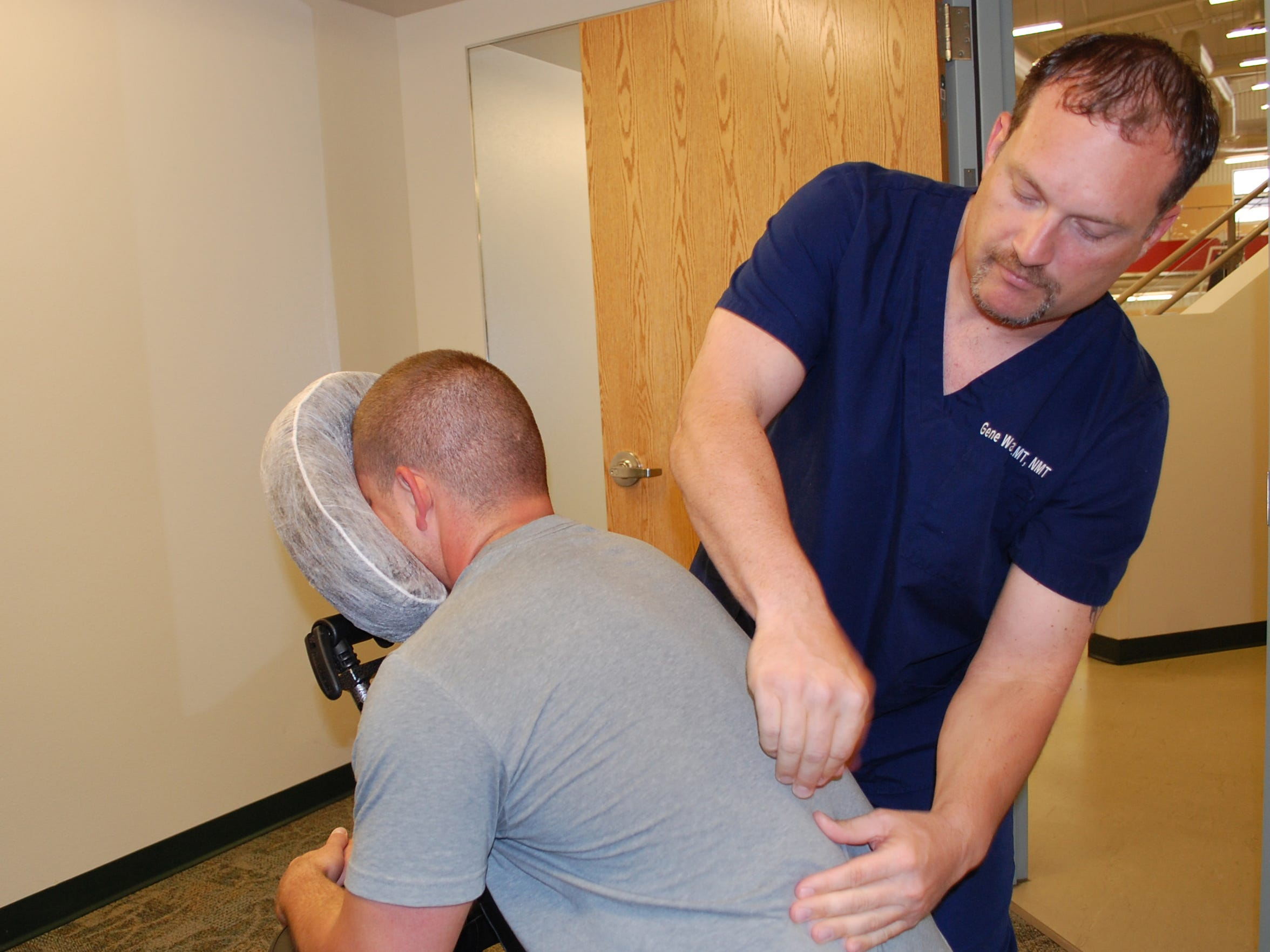 Licensed Massage Therapist Gene Watson performs a chair