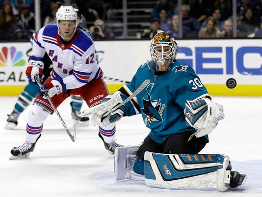 San Jose Sharks goaltender Aaron Dell (30) deflects a shot next to New York Rangers center Peter Holland during the first period of an NHL hockey game Thursday, Jan. 25, 2018, in San Jose, Calif. (AP Photo/Marcio Jose Sanchez)