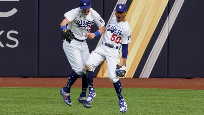 Los Angeles Dodgers right fielder Mookie Betts celebrates with center fielder Cody Bellinger after robbing Atlanta Braves' Marcell Ozuna of a home during the fifth inning in Game 6 of a baseball National League Championship Series Saturday, Oct. 17, 2020, in Arlington, Texas.