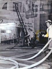 Cincinnati police, with guns drawn, patrol among fire hoses on Burnet Avenue during 1967 riot.