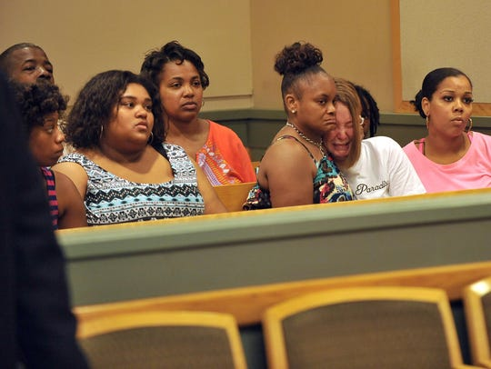 Family and friends of the late Christian Gibson watch