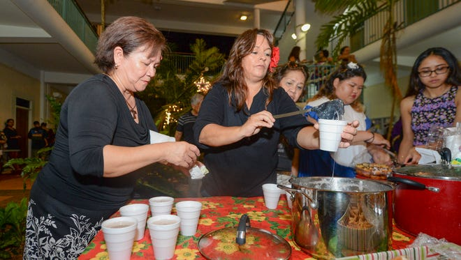 University of Guam student Tracey Calvert, center, serves up cups of ahu, or warm coconut dessert soup, during the Puengen Minagof Nochebuena holiday event at the University of Guam in Mangilao on Friday, Dec. 4.
