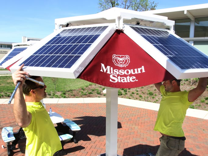 Joe Kobus, left, and Corey Culy of Michigan company EnerFusion set up a solar powered picnic table during Students for a Sustainable Future's Ecopalooza event at MSU on Friday, April 25, 2014.