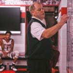 New Albany coach Jim Shannon goes over some strategy during halftime in the Bulldogs' locker room.