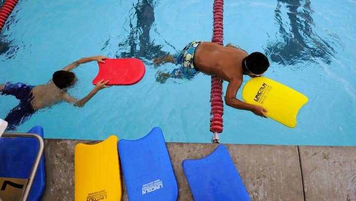 Children swim in the LA Swim Stadium Pool on May 20,
