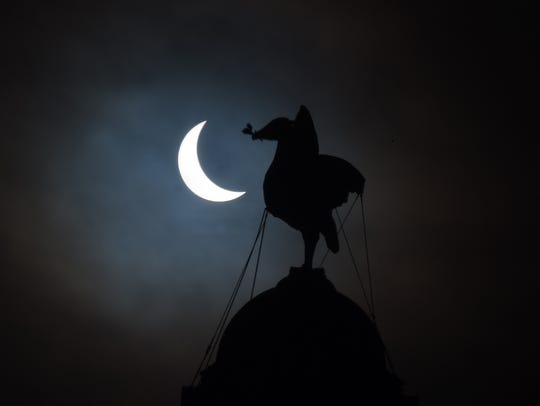 A partial solar eclipse of the sun is visible next